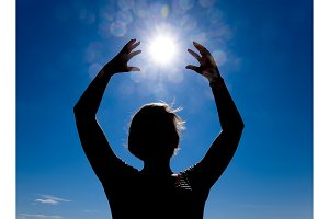 Silhouette of a girl against the background of the sun and blue sky. Hands are raised up to the sun
