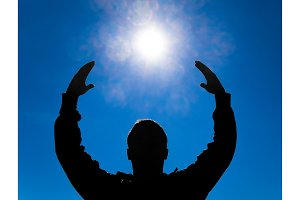Silhouette of a man against the background of the sun and blue sky. Hands are raised up to the sun