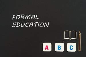 ABC letters and chipboard miniature on blackboard with text formal education