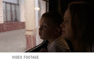 Mother and son in train looking