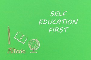 School supplies wooden minitures with text self education first on green background