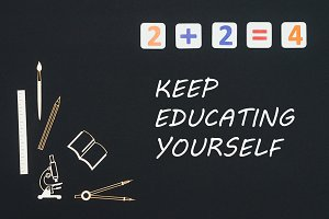 School supplies placed on black background with text keep education yourself