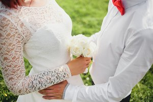 Bride and groom sensually embracing with wedding bouquet in hands