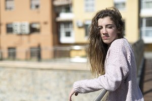 Teen girl resting on a handrail.