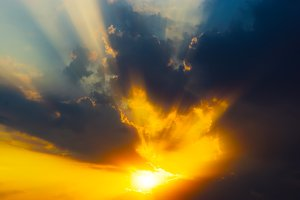 Dramatic sunset rays through cloudscape background