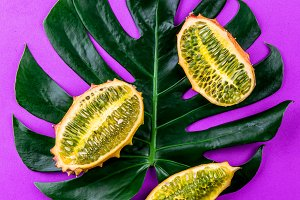 Creative layout made of summer tropical fruits and tropical leaves monstera on purple background. Flat lay. Tropical food concept.