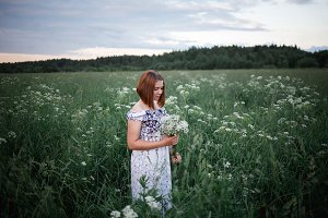 Beautiful brunette in the evening summer field with bouquet of meadow flowers