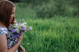 Beautiful young woman with bouguet meadow flowers enjoying field aromas.