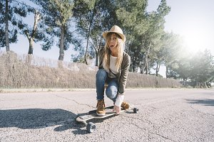 Blonde woman with hat riding on skat