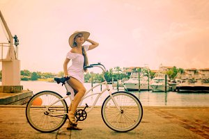 Girl in white dress on a bicycle