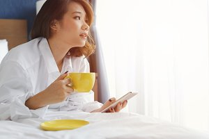Woman with coffee morning on bed