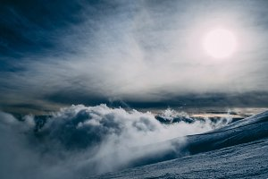 Clouds on a snowy mountain