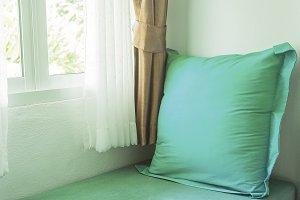 light green pillow near in window