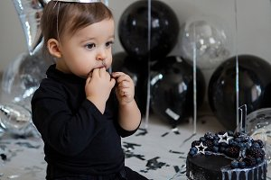 boy stands next to a festive black cake