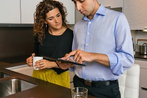 Couple looking electronic tablet at breakfast in home