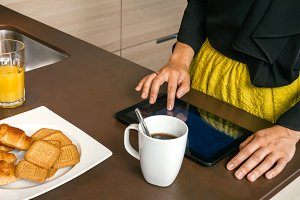 Closeup of woman using electronic tablet at breakfast