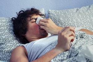 Sick man sneezing and holding thermometer on bed