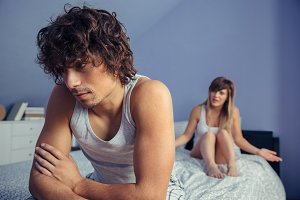 Man sitting over bed listening to woman in quarrel
