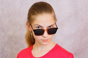 A teenage girl in the pinhole glasses.Studio shot
