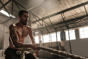 Fitness man pulling rope at gym