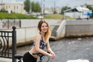 Young athletic woman wearing bicycle helmet,standing by bicycle