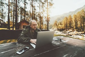 Businessman with laptop in moutains
