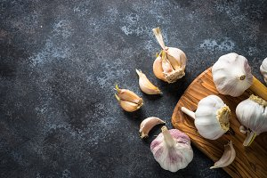 Garlic cloves on a dark stone background.