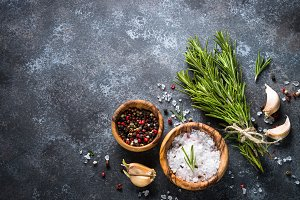 Sprigs of rosemary, pepper and garlic on a dark stone background