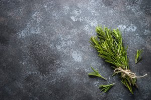 Sprigs of rosemary on black top view.