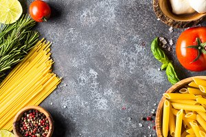 Italian food background. Pasta, herbs, vegetables on black top v