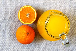 Jug of orange juice and ripe oranges