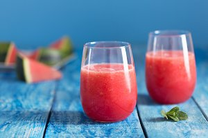 Fresh watermelon smoothie in two glasses on a blue wooden rustic background