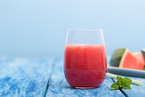 Fresh watermelon smoothie in a glass on a blue wooden rustic background with copyspace