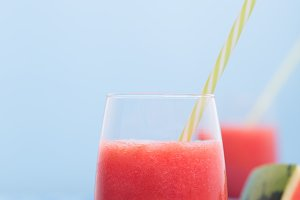 Fresh watermelon smoothie in two glasses on a blue wooden rustic background. Photo with copyspace, vertical orientation.