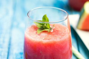Fresh watermelon smoothie in two glasses on a blue wooden rustic background. Closeup shot.