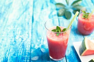Fresh watermelon smoothie in two glasses with a straw and a piece of fruit on a blue wooden rustic background wth copyspace