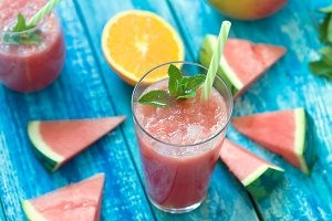 Fresh watermelon and orange smoothie in a glass on a blue wooden rustic background