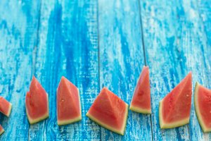 Watermelon pieces on a blue wooden rustic background with a copy space