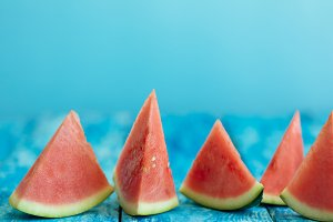 Watermelon pieces on a torquoise wooden rustic background with a copy space, closeup shot
