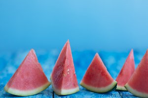 Watermelon pieces on a blue wooden rustic background with a copy space, closeup shot