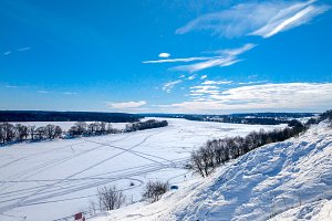 Winter landscape of river. Beautiful lake background with trees and blue sky. Clear blue sky with clouds.