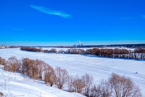 Frozen river winter covered with snow. Beautiful lake landscape in ice. Clear blue sky with clouds.