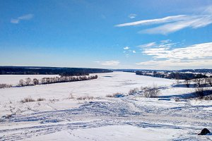 Frozen river in winter covered with snow. Beautiful lake landscape in ice. Clear blue sky with clouds.
