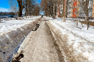 The cleared road in the park, cleaned in winter in city, the road cleaned by a sunny day. Asphalt in snow next to the fence.