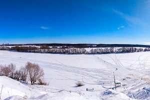 Ponarama winter landscape of nature. The river Oka froze and covered with snow. In nature in winter in Russia. Clear blue sky with clouds. Footprints in the snow from people.