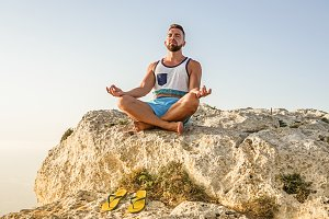 Bearded adult man making lotus pose
