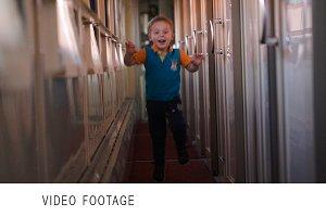 Happy boy running along the train