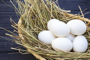 chicken eggs in a basket with hay