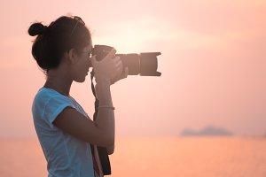young woman photographer, taking pictures of landscape at sunset
