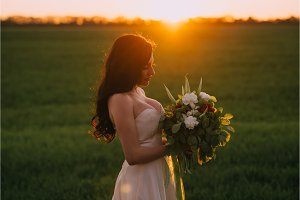 portrait of a bride with a bouquet in hands at sunset